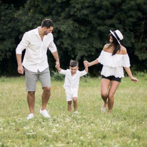 一對爸媽在草地上牽著小兒子