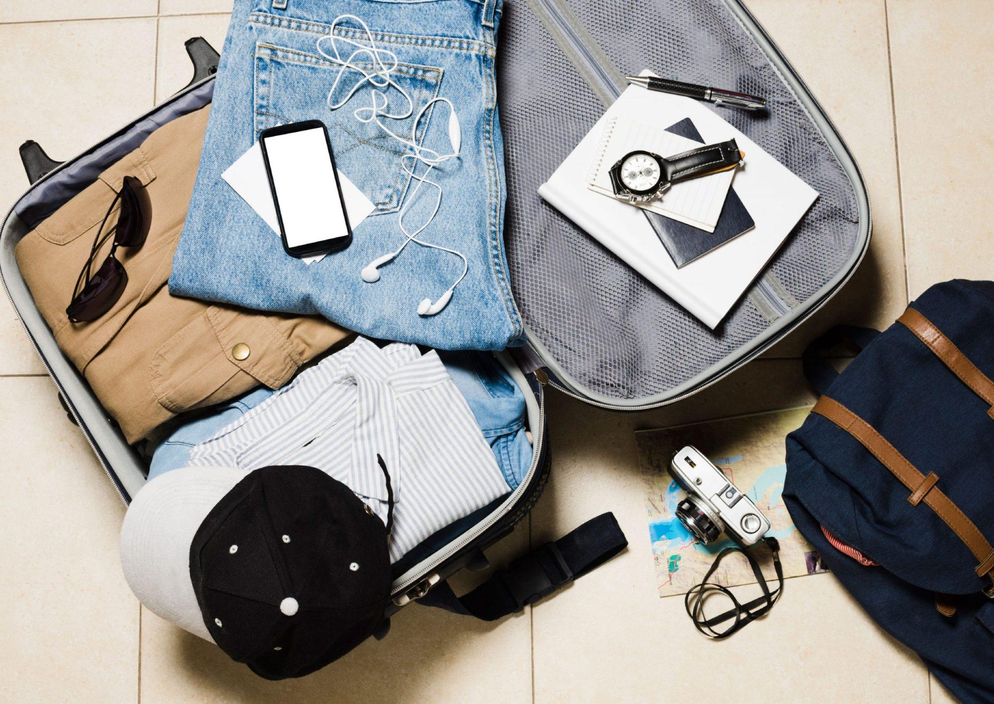 出國必備工具:男性行李箱攤開有帽子手錶護照相機手機牛仔褲