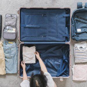 出國必備工具:女性收拾行李他帶了牛仔褲上衣背包盥洗用具