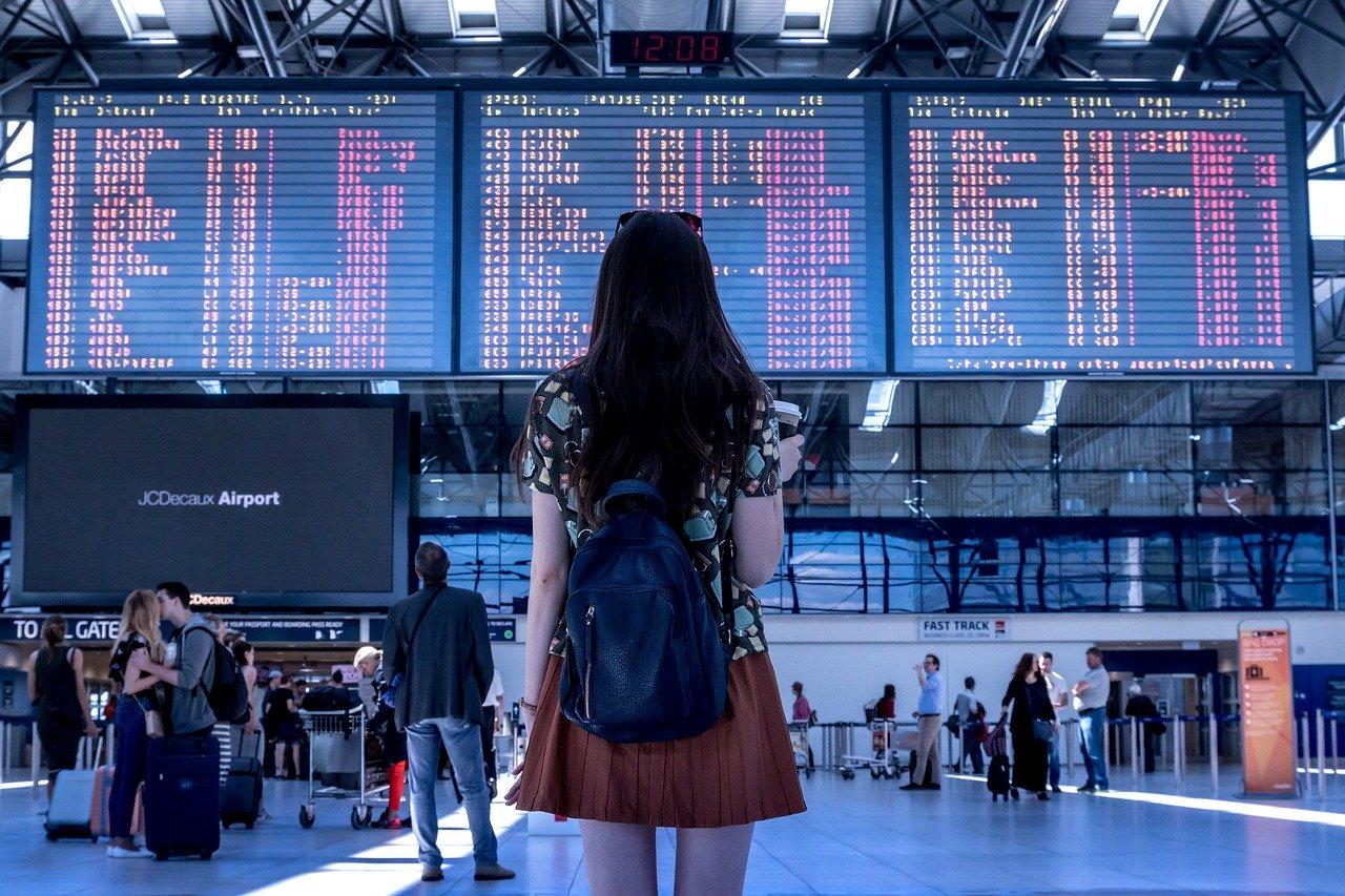 一名穿紅色裙子黑色長髮在機場看著飛機航班表