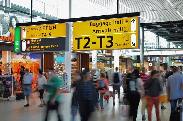 機場人多大家忙碌感飛機的樣子黃色看板寫著出口及抵達