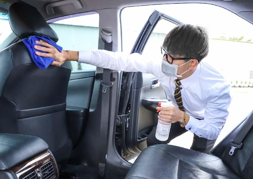 司機戴著口罩右手拿酒精噴霧左手拿抹布消毒車內