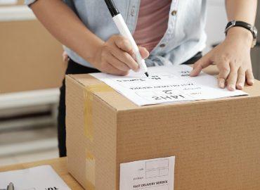 穿著襯衫拿著簽字筆寫包裹上的寄送資訊準備寄出包裹