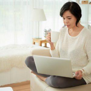穿白色長袖灰色褲子拿著咖啡看著電腦影片的女生