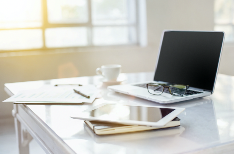 桌上有一台筆電,筆電上有眼鏡。桌上有輸有平板有紙筆有咖啡