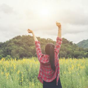 一個穿紅格子襯衫的綁馬尾女生在草原中高舉雙手