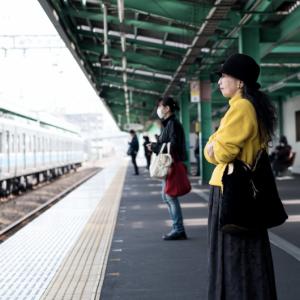 一名穿黃色衣服女子在月台等車