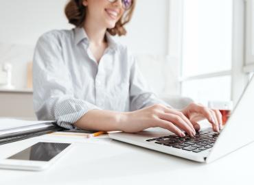 一名穿白色衣服女子在使用電腦申請防疫補償金