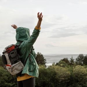 綠色外套背著背包爬山旅行的人