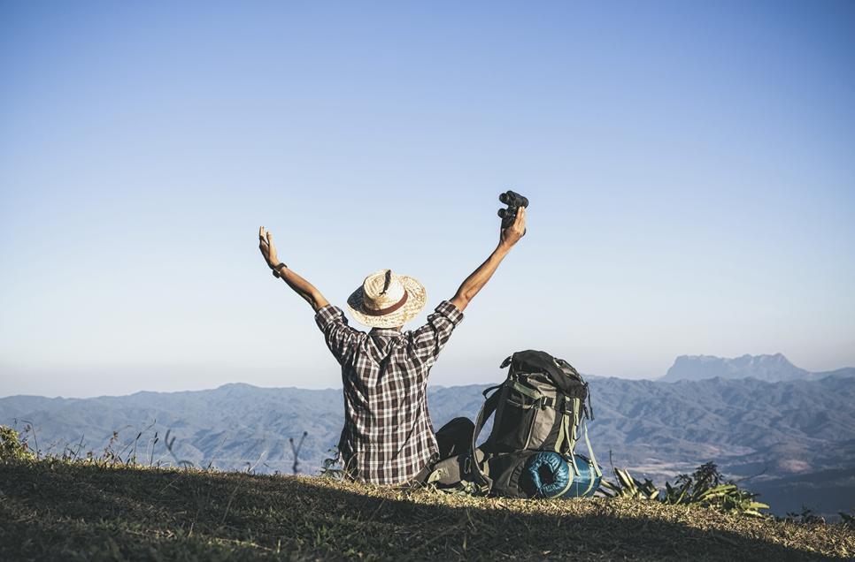 一名格子襯衫戴著帽子在旅行的男子