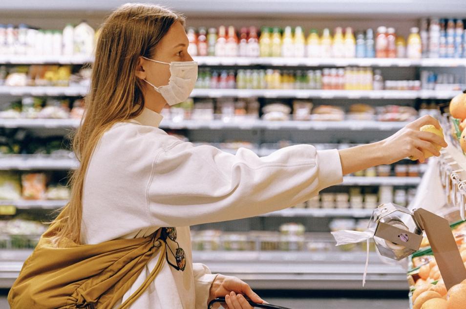 一名白色衣服黃色背包帶著口罩的女子在超市買東西