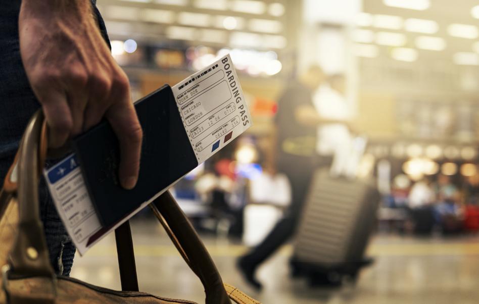 一名男子手拿著行李加上護照機票準備要出國